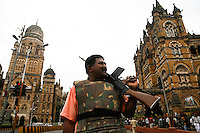 An armed policeman patrols near Chhatrapati Shivaji Terminus amidst rumours of another shootout. The train station, formerly Victoria Terminus and better known as CST or Bombay VT, was one of the targets of the multiple terrorist attacks on the city on 26/11/2008.