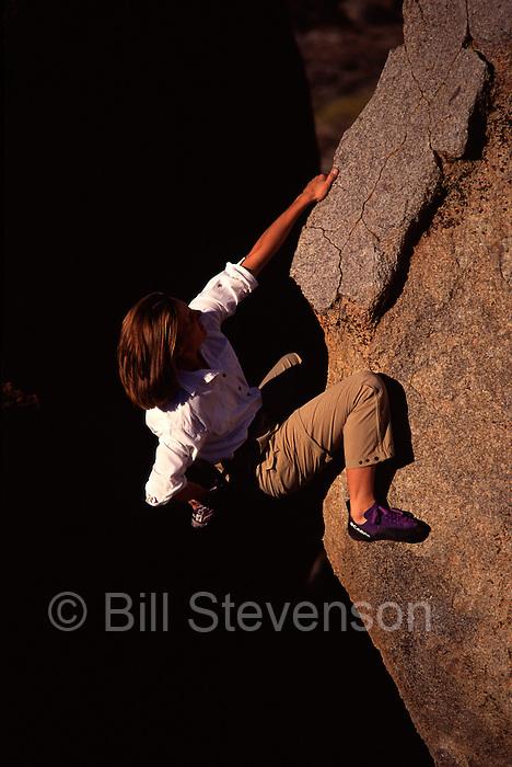 A woman  rock climbing at The Buttermilks, CA.