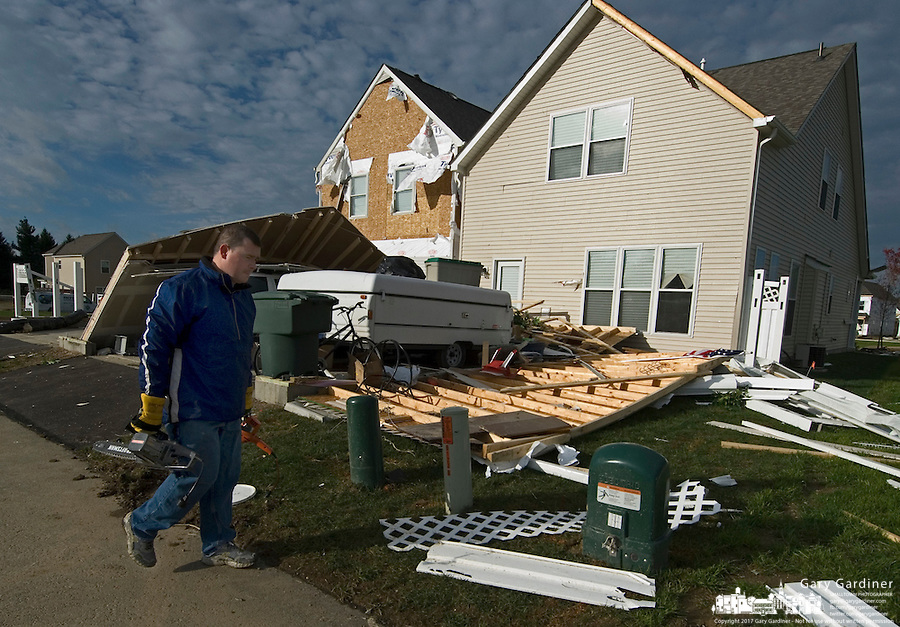 Dana Thacker carries power tools he retrieved from debris walks past his mother-in-law's house the morning after it was damaged by a tornado near Columbus, Ohio, Wednesday, Oct. 11, 2006.<br />