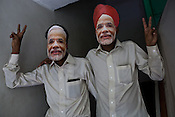 Bhartiya Janta Party (BJP) workers show a victory sign while wearing a face mask of Gujarat's Chief Minister, Narendra Modi at the BJP party office in Ahmedabad, Gujarat, India