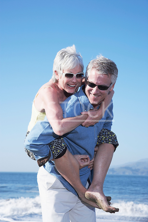 USA, California, Fairfax, Happy mature man giving piggy back ride to woman on beach