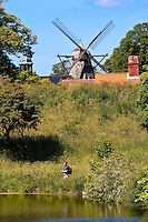 Man fishing in a pond in front of a historical windmill in Copenhagen, Denmark.