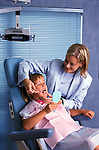 friendly dentist holding mirror for young girl to see her teeth while he teaches correct toothbrushing technique