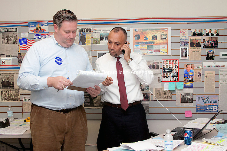 WATERBURY CT- NOVEMBER 06 2011 -110612DA01- 75th State House District candidate Democratic Victor Cuevas, right, goes over polling numbers with J. Paul Vance Jr. at Cuevas' headquarters on Grand St. in Waterbury Tuesday night. Cuevas is running against John F. Alseph Jr..Darlene Douty Republican-American