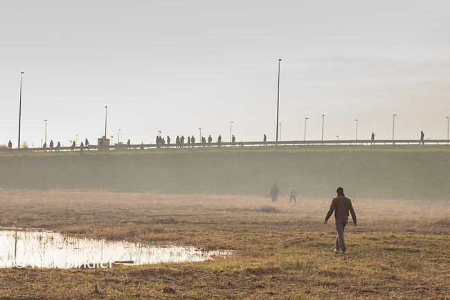 FRANCE, Calais: 17 December 2015 A refugee walks toward other refugees amongst a cloud to tear gas outside of the Euro Tunnel entrance in Calais this afternoon. Hundreds of refugees walked hours through Calais today to reach the Euro Tunnel from 'The Jungle' camp to try and get to England. Rick Findler  / Story