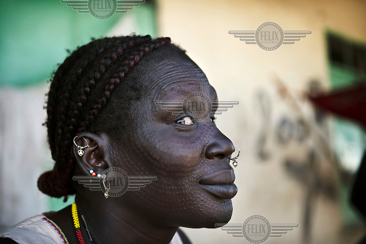 A woman with elaborate scarification marks sits outside a referendum centre where people can register themselves for the upcoming referendum on independence. Many Sudanese, who fled Sudan during the civil war, are returning home, mainly to participate in the upcoming referendum in January 2011, when South Sudan will vote on its independence.