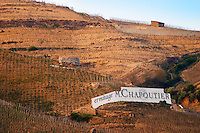 The vineyard and sign Ermitage of M Chapoutier, just below the chapel. The Hermitage vineyards on the hill behind the city Tain-l'Hermitage, on the steep sloping hill, stone terraced. Sometimes spelled Ermitage. Tain l'Hermitage, Drome, Drôme, France, Europe
