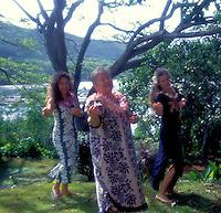 Three women dancing hula at Heeia state park near ocean and trees