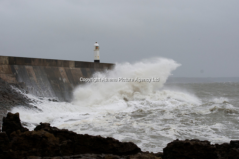 Pictured: Waves hit Porthcawl lighthouse in  Bridgend, Wales, UK. Wednesday 19 September 2018