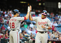 Jun. 2, 2011; Phoenix, AZ, USA; Washington Nationals shortstop Ian Desmond (right) is congratulated by teammate Danny Espinosa after scoring in the first inning against the Arizona Diamondbacks at Chase Field. Mandatory Credit: Mark J. Rebilas-