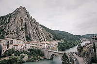 peloton riding through the town of Sisteron with it's distinctive monumental rock formations<br /> <br /> 104th Tour de France 2017<br /> Stage 19 - Embrun &rsaquo; Salon-de-Provence (220km)