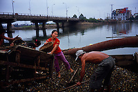 Workers shovel gravel and stones off a barge in Dong Hoi, VIetnam on 23 February 2010.