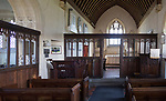 Wooden chancel screen dating from 15th - 16th century looking down to altar and east window inside the church at Charlton, Wiltshire, England, UK