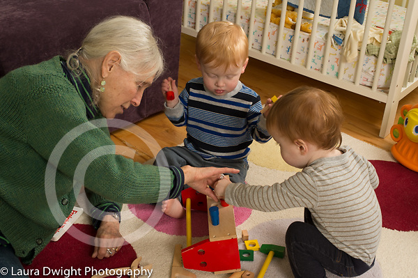 20 month old toddler fraternal twin boys playing with their grandmother and wooden toolbox and tools, child care, she takes care of them twice a week