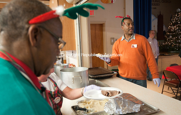 WATERBURY, CT--- -122515JS04--Winston Stephenson, left, and his brother Fred Stephenson, right, were two of the many volunteers who cooked and served dinners during the annual Christmas Dinner Friday at the First Congregational Church in Waterbury. <br /> Jim Shannon Republican-American