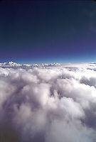 Aerial, high-altitude view of a cloud bank under a wide blue sky.