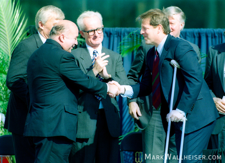 Historic photo of US Vice President (R) shakes hands with Charles Reed, Chancellor of the Florida Board of Regents after Gore's speech at the National High Magnetic Field Laboratory in Tallahassee, Florida October 1, 1994.  Gore is on crutches from surgery to repair a torn Achilles tendon.
