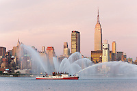 "WEEHAWKEN, NJ - JULY 4: FDNY fire boat Marine 9 ""Fire Fighter"" puts on a water show on the Hudson river, with the Empire State Building and Manhattan skyline in the background, prior to the annual Macy's Fourth of July fireworks on Friday, July 4, 2009."
