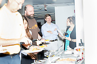 John Fawcett, the CEO and co-founder of Quantopian, (in light blue shirt) gathers with employees during a team lunch meeting about company policies in the offices of Quantopian in the Downtown Crossing area of Boston, Mass., on Wed., June 1, 2016. Quantopian is a Boston-based start-up that provides a platform for building, testing, and executing stock trading algorithms.
