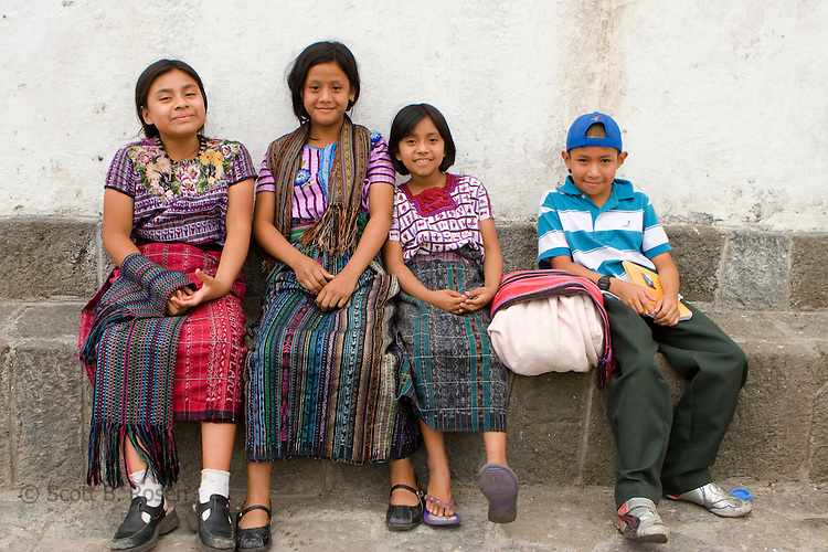 Guatemalan children in traditional dress relax outside a church in Santiago Atitlan, Guatemala