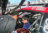 Juan Monoya shows his son , Sebastian, the cockpit of his race car before the Rolex 24 at Daytona, Daytona International Speedway, Daytona Beach, FL, January 2011.  (Photo by Brian Cleary/www.bcpix.com)