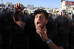 A Palestinian shouts slogans in front of riot police during a demonstration against the newly cooperation between the Palestinian police with the Israeli police to find three missing Israeli teenagers, in the center of the West Bank city of Ramallah, June 23, 2014. Since the youths disappeared from a hitchhiking stop in the southern West Bank on June 12, Israel has rounded up hundreds of Palestinians in a bid to find them, while also crushing the West Bank network of Islamist movement Hamas, which it accuses of abducting the teens. Photo by Issam Rimawi