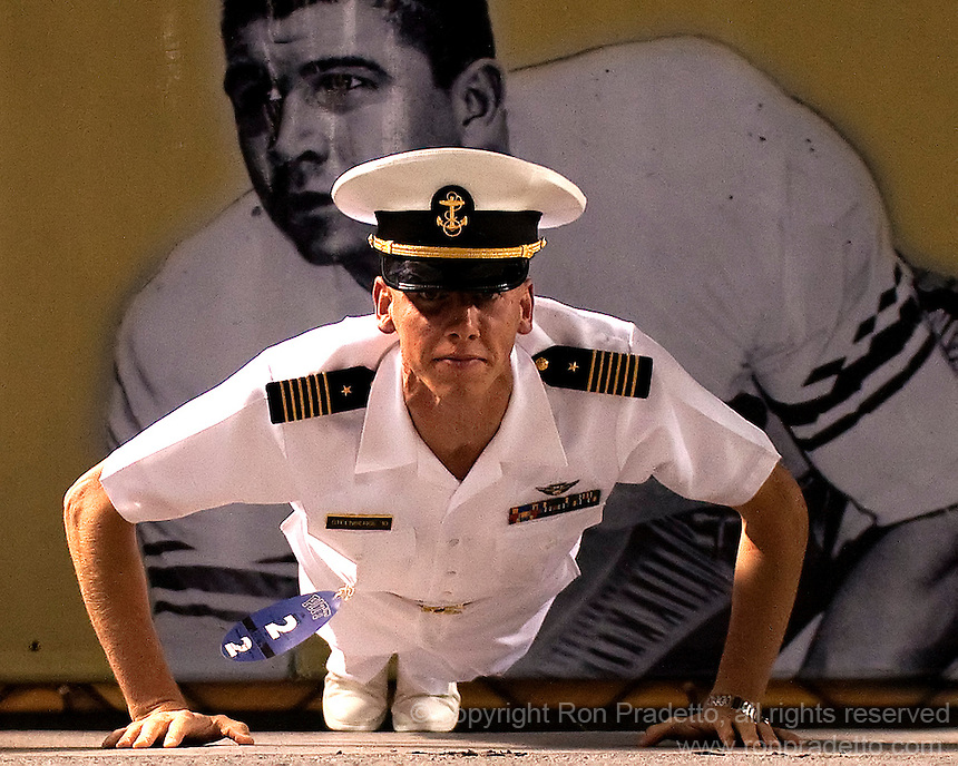 A Navy midshipman does pushups after a touchdown in front of an image of Pitt Hall of Famer Mike Ditka. The Pittsburgh Panthers defeated the Navy Midshipmen 27-14 at Heinz Field, Pittsburgh, PA.