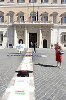 Roma,11 Agosto 2011.Piazza Montecitorio.Manifestazione dell'IDV davanti il Parlamento durante l'informativa di Tremonti sulla manovra economica.Stefano Pedica compone una croce con magliette