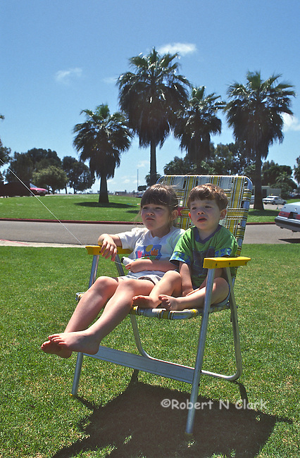 Boy and girl sharing a chair in the park
