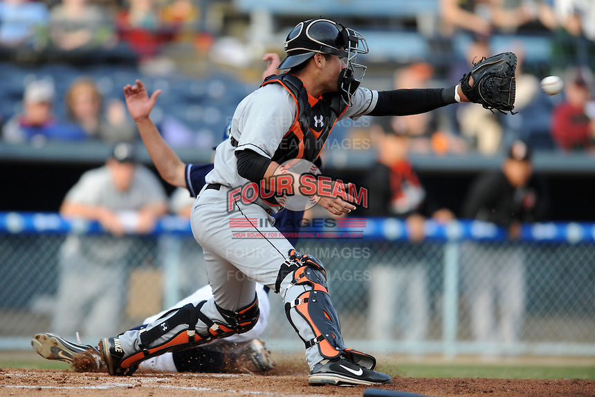 Delmarva Shorebirds catcher Austin Wynns #12 fields the ball as Michael Benjamin #18 slides in safely during a game against the  Asheville Tourists at McCormick Field on April 5, 2014 in Asheville, North Carolina. The Tourists defeated the Shorebirds 5-3. (Tony Farlow/Four Seam Images)