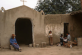 Chiclayo, Peru. A man, a wonman and two children sitting outside a simple adobe brick church with two cats.