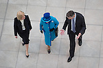 © Joel Goodman - 07973 332324 . 14 November 2013 . Manchester , UK . The Queen (in blue) crosses the foyer . Queen Elizabeth II and the Duke of Edinburgh visit the Coop building at 1 Angel Square , Manchester , this morning ( 14th November 2013 ) . Photo credit : Joel Goodman