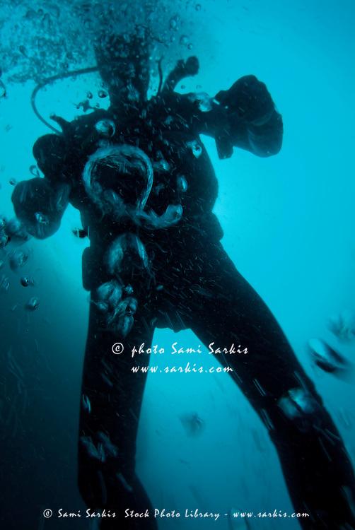 Bubbles surrounding a scuba diver underwater, France.
