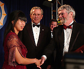 """Washington, D.C. - May 21, 2005 -- United States President George W. Bush, center, and  Nhanny Heil, left, congratulate Chick Herrity, right, as he receives the White House News Photographers Association (WHNPA) """"Lifetime Achievement Award"""" at the annual """"Eyes of History"""" Gala in Washington, D.C. on May 21, 2005.  Ms. Heil was photographed by Mr. Herrity in Saigon, Vietnam where she was orphaned.  The photo of Ms. Heil is one of Mr. Herrity's award winning photos.  She lives in the United States with her adoptive parents.  <br /> Credit: Ron Sachs - Pool via CNP"""