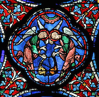 2 thurifers or incense-bearer angels swinging censers above the funeral procession of Mary as a mark of respect and honour for the dead, from the Glorification of the Virgin stained glass window, in the nave of Chartres Cathedral, Eure-et-Loir, France. This window depicts the end of the Virgin's life on earth, her dormition and assumption, as told in the apocryphal text the Golden Legend of 1260. Chartres cathedral was built 1194-1250 and is a fine example of Gothic architecture. Most of its windows date from 1205-40 although a few earlier 12th century examples are also intact. It was declared a UNESCO World Heritage Site in 1979. Picture by Manuel Cohen