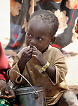 A newly arrived Somali refugee child eats while waiting to be registered in the Dadaab refugee camp in northeastern Kenya. Tens of thousands of newly arrived Somalis who have swelled the population of what was already the world's largest refugee camp. The boy's yellow wristband means he has been received but not yet registered.