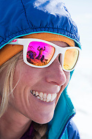 A woman smiles as her sunglasses reflect another happy skier
