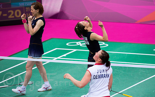 28 JUL 2012 - LONDON, GBR - Suetsuna Satoko (JPN) (second from left) and Maeda Miyuki (JPN) (left) of Japan celebrate winning their London 2012 Olympic Games women's doubles group badminton match against Kamilla Rytrer Juhl and Christinna Pedersen of Denmark at Wembley Arena, London, Great Britain .(PHOTO (C) 2012 NIGEL FARROW)