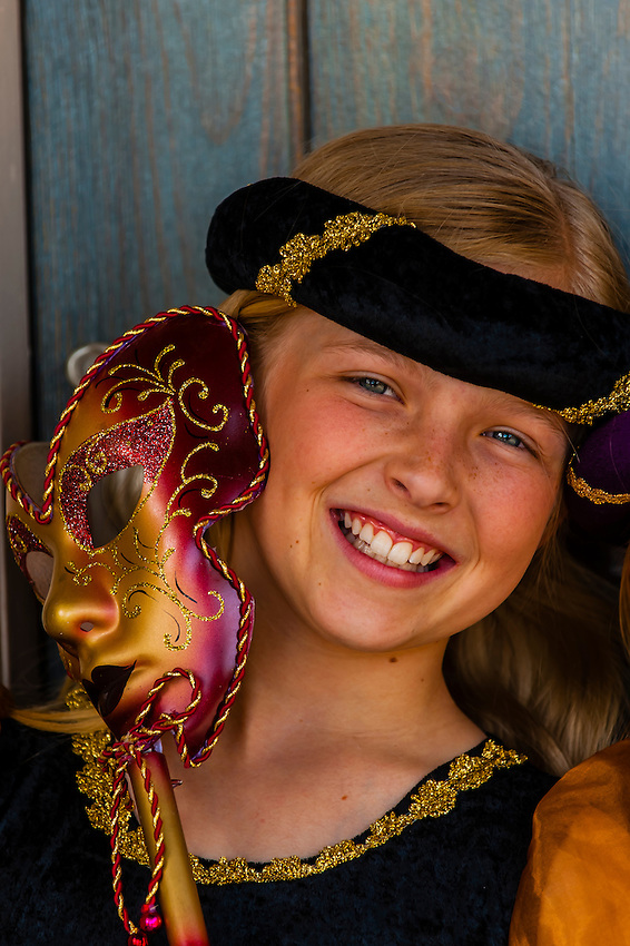 Preteen girl dressed in medieval costume (and holding a Carnival mask), Cedar City, Utah USA. Cedar City is home to the Tony Award-winning Utah Shakespeare Festival.