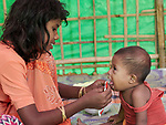 Shortly after they made the perilous crossing from Myanmar into Bangladesh, a girl feeds her younger sibling in a United Nations clinic for severely malnourished Rohingya children in the Balukhali Refugee Camp near Cox's Bazar, Bangladesh. She is using Plumpy'nut, a peanut-based supplement given to malnourished children. <br /> <br /> More than 600,000 Rohingya have fled government-sanctioned violence in Myanmar for safety in Bangladesh.