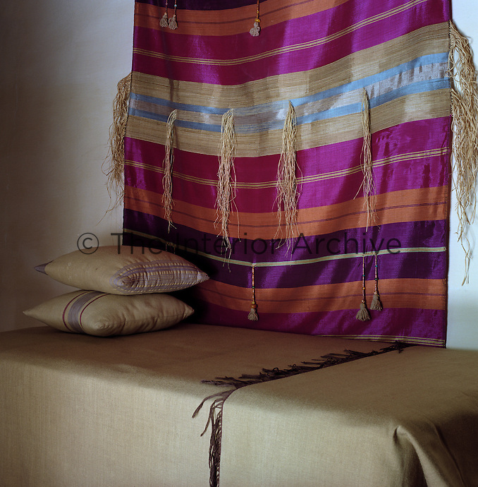 Local woven textiles are used as a wall hanging and as a bedcover in this bedroom