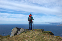 Female hiker with view over sea from Ytresandheia, Moskenesøy, Lofoten Islands, Norway