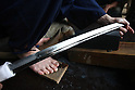 June 26, 2010 - Tokyo, Japan - A Japanese sword expert inspects a long sword (katana) during The 1st Sword Craftsmen Exhibition of the NBSK (Nihon Bunka Shinko Kyokai) at Okura Musem of Art located in Okura Hotel in Tokyo, Japan, on June 26, 2010. The event runs from June 13 to July 25 and let sword masters show their skills such as sword polishing, sword fittings and mounting to visitors.