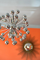 A chrome Sputnik pendant light illuminates the dining area