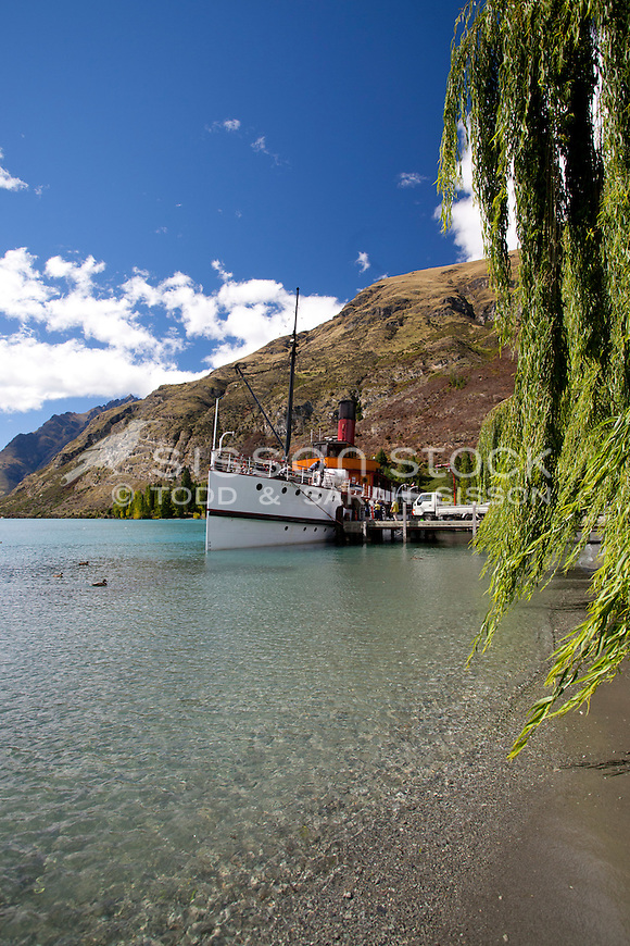 TSS Earnslaw summers day Walter Peak Station, blue sky, Cecil Peak in background, green willow in shot, Queenstown, Lake Wakatipu, New Zealand
