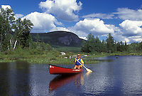 canoeing, canoe, Vermont, VT, Woman paddling a red canoe on Marshfield Pond in Marshfield.blue sky and puffy clouds.