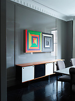 The dining room is decorated in cool grey panelling and has polished dark wood parquet flooring. A vintage ceiling light hangs above the large square dining table, which sits eight. A Charlotte Perriand sideboard sits beneath a Frank Stella artwork. The chairs by Paul Laszlo are upholstered in a Knoll Ultrasuede.