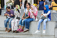 Young Singaporean Women in Conservative and Casual Western Clothes Sitting outside ION Mall.  Singapore, Orchard Road Street Scene.