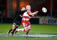 Photo: Richard Lane/Richard Lane Photography. Gloucester Rugby v Stade Toulouse. Heineken Cup. 20/01/2012. Gloucester's Scott Lawson passes as he is tackled by Toulose's Luke Burgess.