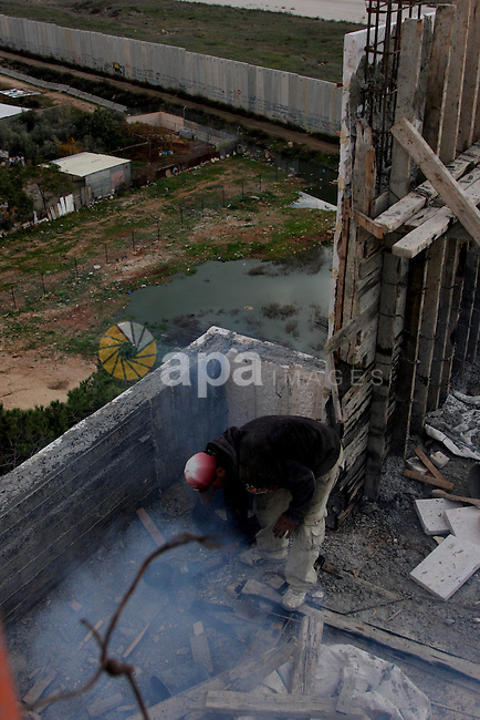 Palestinian works near the Israel's controversial separation barrier, near  Qalandia refugee camp,in the southern of Ramallah City in the West Bank, on Dec 6, 2009. Photo by Issam Rimawi